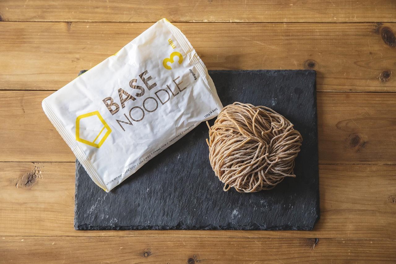 「ベースヌードル」からリニューアルした「ベースパスタ」。26種のビタミン&ミネラル、29.8gのたんぱく質、6.9gの食物繊維など、からだに必要な栄養素がぎゅっとつまった完全栄養パスタ。